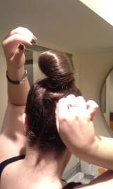 Step 4: Wrap the ends around the base of the bun, between your head and the lower loops, and tuck them in.